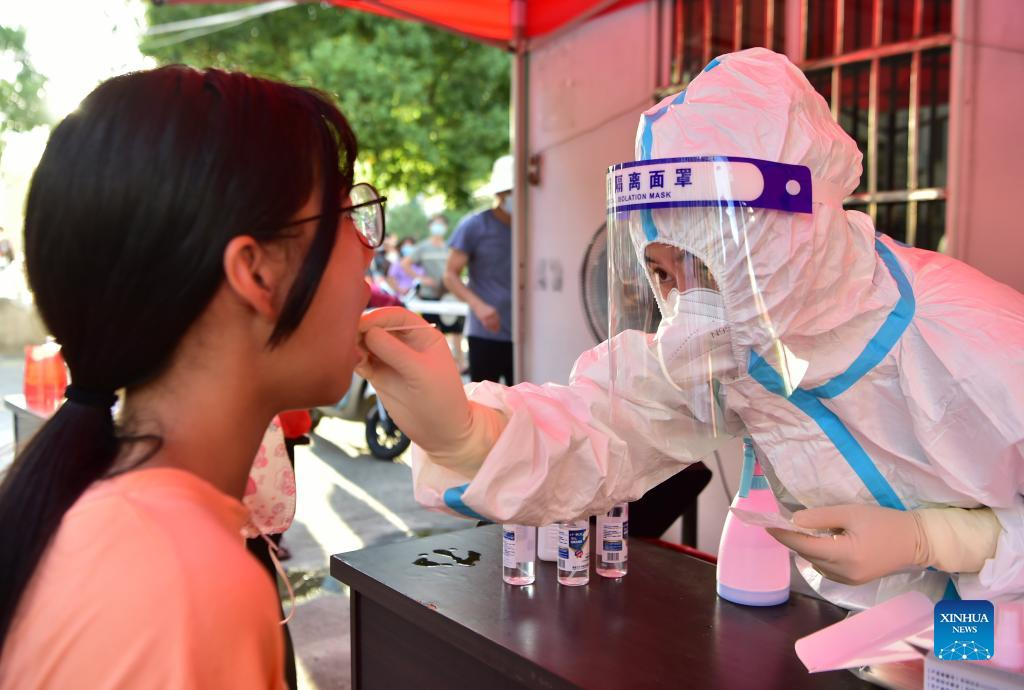 A health worker collects swab sample from a resident for COVID-19 test in Xianyou county